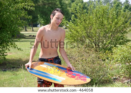 Picture of male teen trying to skimboard in backyard pool.