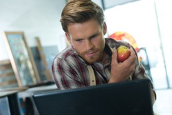 picture of male worker holding apple fruit checking laptop