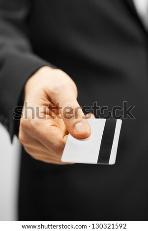 picture of man in suit holding credit card.