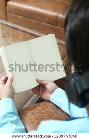 Picture of man is holding book in hand and listening music with headphone.