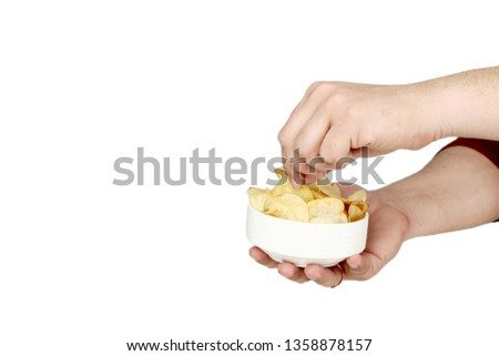 Picture of man is holding in one hand potato chips in the bowl and other hand is picking chips. Isolated on the white background.