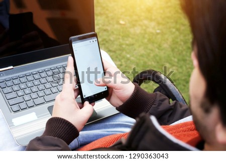 Picture of man is using smartphone with laptop.