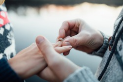 Picture of man putting engagement silver ring on woman hand, outdoor. Sea or river background.