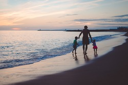 Picture of man walking with boy and girl on sunset beach. Silhouette of happy family beside seawaves on dark blue seaside outdoor background.