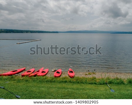 Picture of many kayaks resting on the beach of a gorgeous lake, waiting for people to use them and have a good healthy time.