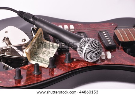 Photo of Picture of microphone and dollar lying on a guitar on a white background