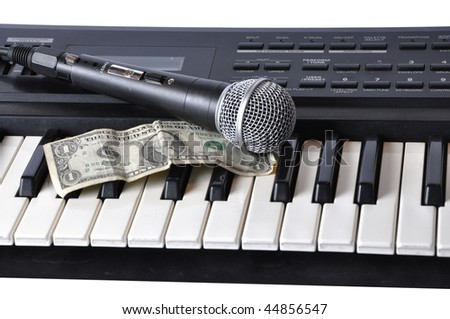 Photo of Picture of microphone and dollar lying on the keys on a white background