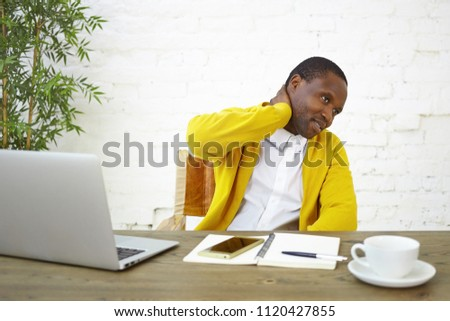 Picture of modern fashionable young dark skinned businessman rubbing neck, feeling frustrated and uncertain about something, sitting at workplace with open laptop, diary, mug and mobile phone on desk
