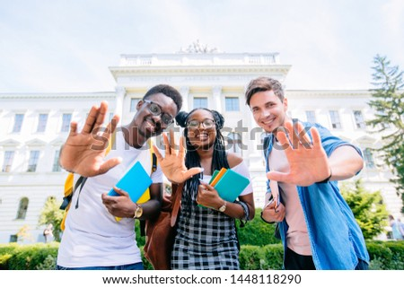 Picture of multiethnic group of young cheerful students standing outdoors waving hands. Looking at camera.