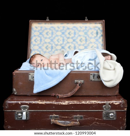 Picture of newborn baby lying in a old suitcase on black background