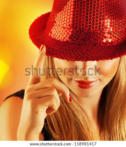Picture of of luxury singer girl isolated on yellow blur background, closeup portrait of pretty woman wearing stylish red hat which covered her eyes, Christmas holiday, New Year party, night lifestyle