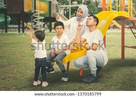 Picture of of Muslim Asian family playing with soap bubbles in the playground. Shot at summer