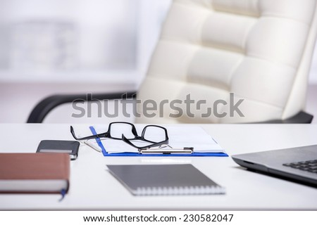 Picture of office desks and chair. Notebook, glasses, and laptop are on the table.