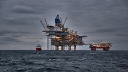Picture of offshore oil and gas production in the sea in stormy weather at dusk. Jack up, semi submersible rigs crude oil production in ocean.