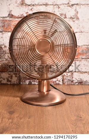 Picture of old style ( brass or copper effect ) electric fan - ventilator with moving blades.