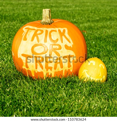 Picture of one big and one small pumpkin, standing on a lawn Small pumpkin has a face cut in the surface, and the big has Trick Or treat cut in the surface