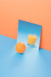 Picture of orange near juice in mirror on blue table isolated over orange background