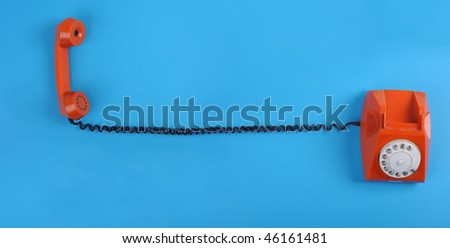 Picture of orange telephone over blue background. Many lot of copyspace