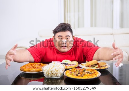 Picture of overweight man hugging at a lot of unhealthy food on the table. Shot at home