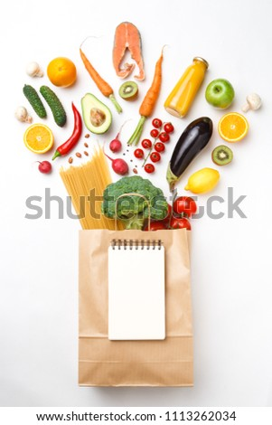 Picture of paper bag with vegetables, fruits and spaghetti isolated on empty white background.