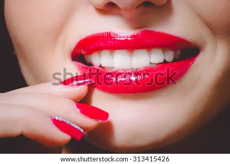 Picture of pearly smile with bright red lips and red nails. Dramatic makeup in red colors on dark indoor background.