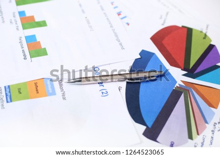 Picture of pen, bar graph and pie chart paper.