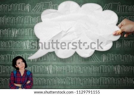 Picture of pensive female college student thinking an idea while looking at an empty cloud bubble. Shot in the library
