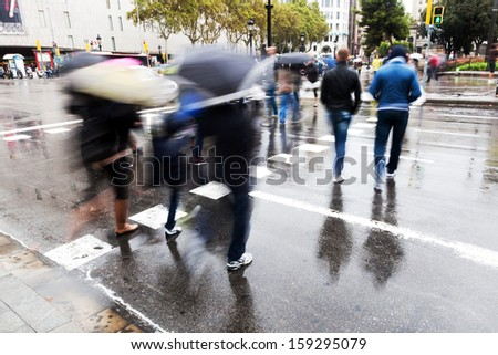 picture of people with umbrellas crossing a street on a rainy day in the city