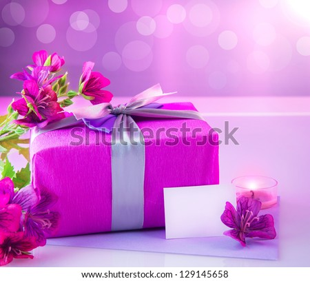 Picture of pink luxury gift box with bouquet of beautiful flowers, romantic candle and postcard with text space on the table, festive still life, blurry background, happy mothers day, spring season