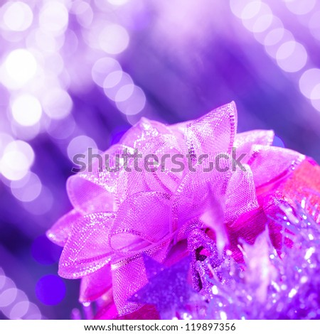 Picture of pink ribbon bow on purple glowing background, Christmas present, New Year gift, holiday decorations, festive ornament, birthday party, Valentines day, celebration concept