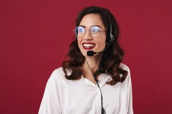Picture of positive smiling young woman work in callcenter isolated over red wall background talking by cellphone.