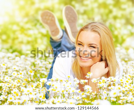 Picture of pretty woman lying down on chamomile field, happy female enjoying spring nature, cheerful girl resting on daisy meadow, beautiful small white flowers, relaxation outdoor in springtime - stock photo