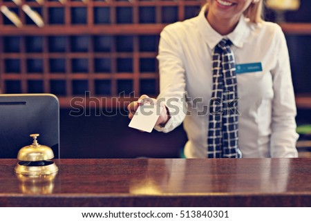 Picture of receptionist giving key card #513840301