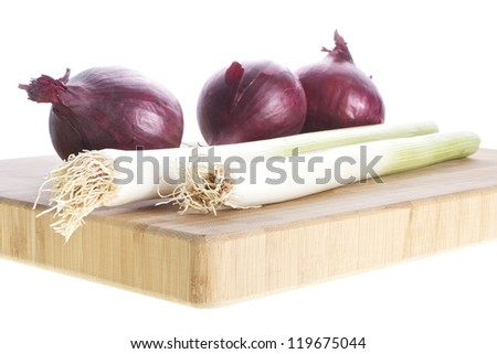 Picture of red onions and leeks on a cutting board