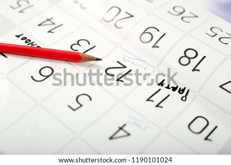 Picture of red pencil on the white calendar page.