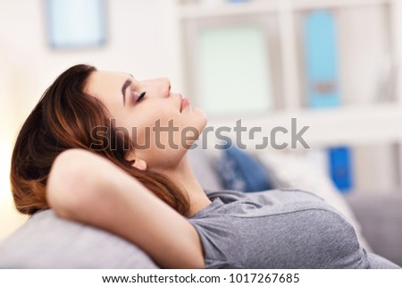 Picture of relaxed young woman enjoying rest on comfortable sofa #1017267685