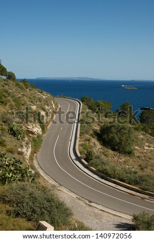 Picture of road turns, with a beautiful sea view and islands in the background