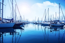 Picture of row of luxury sailboats reflected in water, yacht port on the bay, water transport, ocean transportation, beautiful vessel in the harbor, summer vacation, active lifestyle, holiday concept