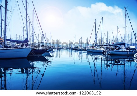 Picture of row of luxury sailboats reflected in water, yacht port on the bay, water transport, ocean transportation, beautiful vessel in the harbor, summer vacation, active lifestyle, holiday concept stock photo