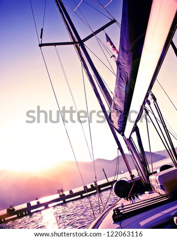 Picture of sailboat on purple sunset, luxury yacht in the sea, romantic vacation and travel, bright light in the sky, peaceful beach view, water sport, freedom and adventure concept