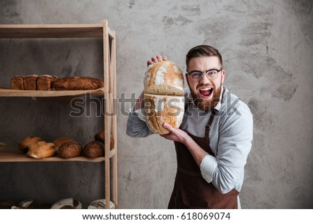 Picture of screaming young man baker standing at bakery holding bread. Looking at camera.