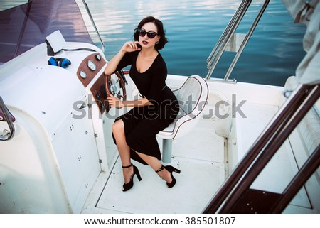 picture of sexy elegant woman sitting on the yacht in black dress and glasses