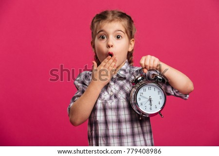 Picture of shocked little girl child standing isolated over pink background. Looking camera holding clock alarm.