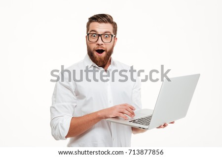 Picture of shocked young bearded man standing over white wall background isolated. Looking camera using laptop.