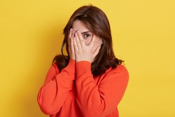 Picture of shy brunette teenage girl covering face with hands and peeping through her fingers at camera. Young attractive female hiding her face being frightened, scared or ashamed, wears casually.