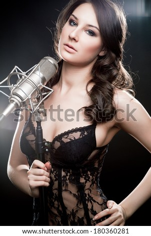 Picture of singer with studio microphone on black