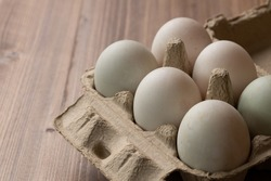 Picture of six egg in a paper box. The egg is white because they are duck egg not a chicken egg. They are organized in two rolls. The paper box is placed on the wooden table.