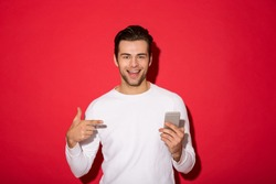 Picture of smiling man in sweater looking at the camera while holding smartphone and pointing at him over red background