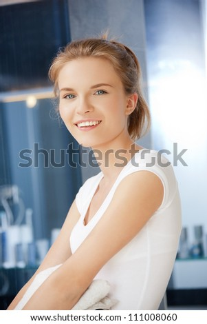 picture of smiling teenage girl with towels in bathroom