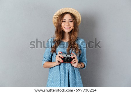 Picture of smiling young caucasian woman photographer holding camera. #699930214
